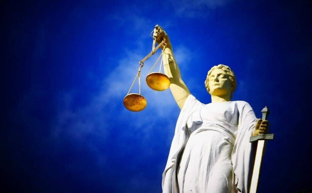 Statue of lady of justice holding scales against a blue sky